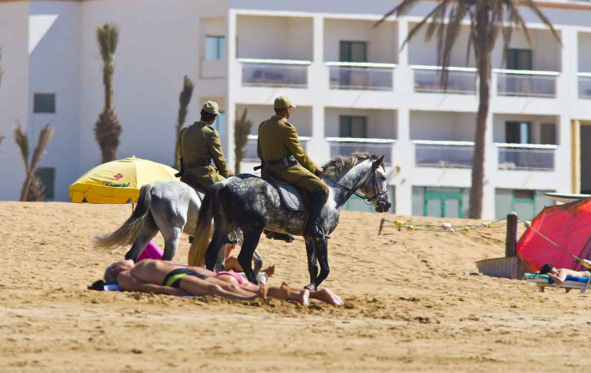 Policia a caballo por las playas de Marruecos